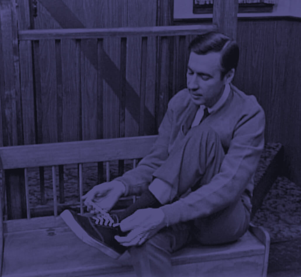Mister Rogers tying his shoe.